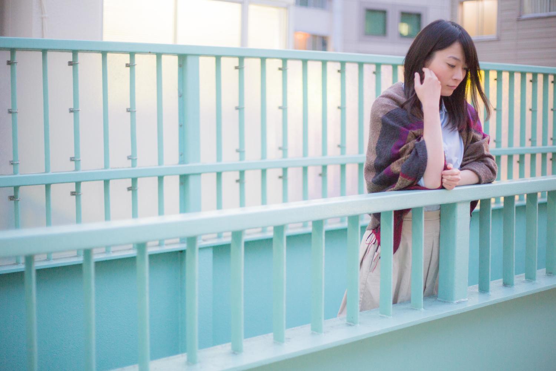橋の上で悩んでいる女性